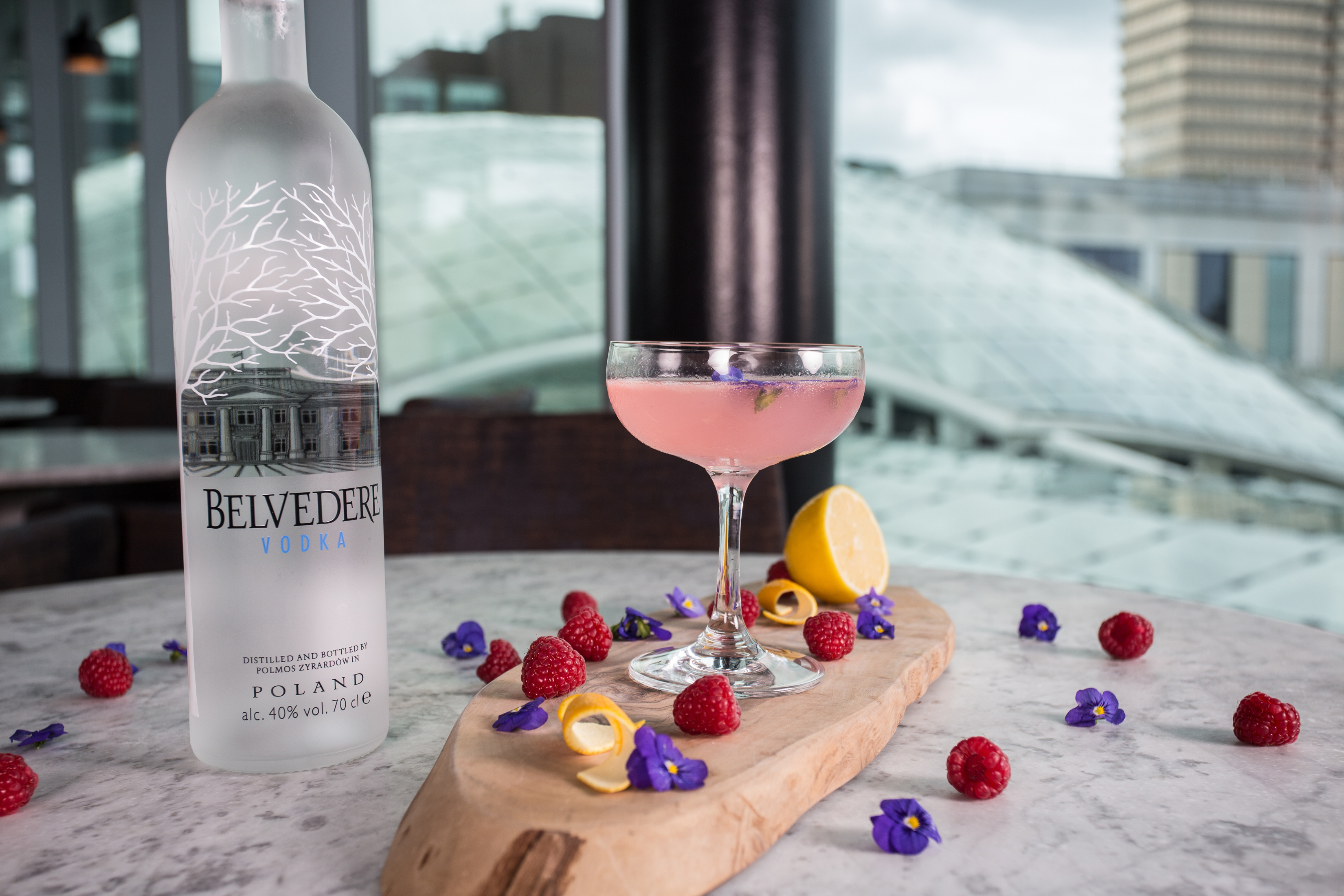 belvedere vodka, raspberries, lemon and flowers in a cocktail