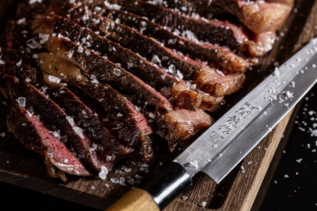 photograph of sliced steak on chopping board with salt and knife